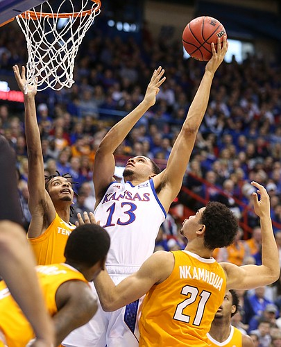 Kansas guard Tristan Enaruna (13) looks for a shot against the Tennessee defense during the first half, Saturday, Jan. 25, 2019 at Allen Fieldhouse.