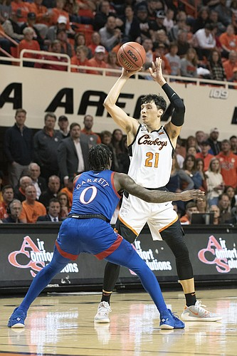Oklahoma State guard Lindy Waters III (21) throws a pass over Kansas guard Marcus Garrett (0) during the first half of an NCAA college basketball game in Stillwater, Okla., Monday, Jan. 27, 2020. (AP Photo/Brody Schmidt)