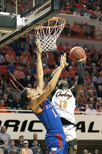 Oklahoma State guard Isaac Likekele (13) takes a shut under pressure from Kansas guard Tristan Enaruna (13) during the first half of an NCAA college basketball game in Stillwater, Okla., Monday, Jan. 27, 2020. (AP Photo/Brody Schmidt)