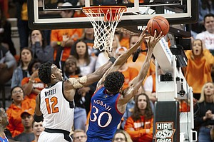 Kansas guard Ochai Agbaji (30) grabs a rebound from Oklahoma State forward Cameron McGriff (12) during the second half of an NCAA college basketball game in Stillwater, Okla., Monday, Jan. 27, 2020. Kansas defeated Oklahoma State 65-50. (AP Photo/Brody Schmidt)