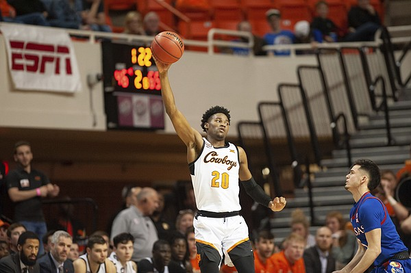 Oklahoma State guard Keylan Boone (20) catches the ball while watching Kansas guard Elijah Elliott (5) during the second half of an NCAA college basketball game in Stillwater, Okla., Monday, Jan. 27, 2020. Kansas defeated Oklahoma State 65-50. (AP Photo/Brody Schmidt)