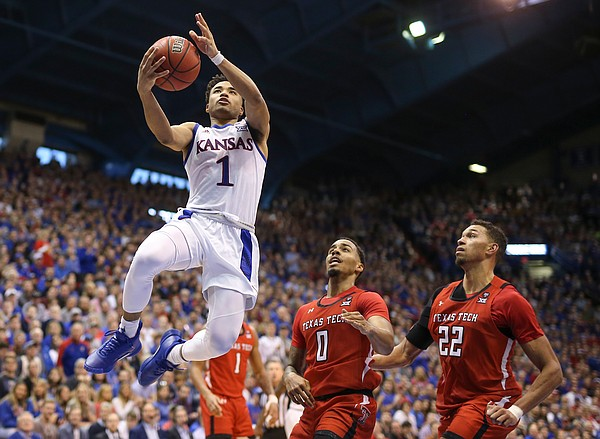 Kansas guard Devon Dotson (1) gets in for a bucket past Texas Tech guard Kyler Edwards (0) and Texas Tech forward TJ Holyfield (22) during the second half, Saturday, Feb. 1, 2020 at Allen Fieldhouse.