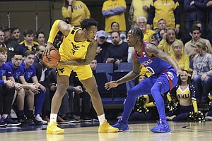 West Virginia forward Gabe Osabuohien (3) looks to pass the ball as Kansas guard Marcus Garrett (0) defends during the first half of an NCAA college basketball game Wednesday, Feb. 12, 2020, in Morgantown, W.Va. (AP Photo/Kathleen Batten)
