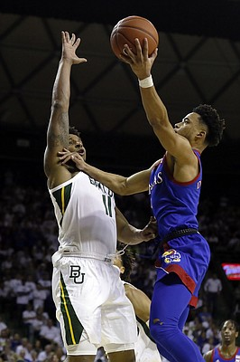 Kansas guard Devon Dotson, right, shoots over Baylor guard Mark Vital, left, during the first half of an NCAA college basketball game on Saturday, Feb. 22, 2020, in Waco, Texas. (AP Photo/Ray Carlin)