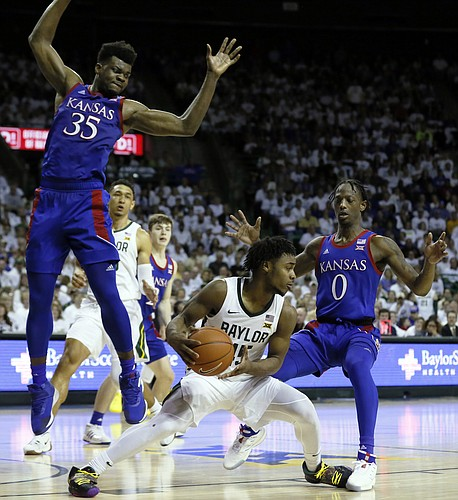 Baylor guard Davion Mitchell, center, is defended by Kansas center Udoka Azubuike, left, and guard Marcus Garrett, right, during the second half of an NCAA college basketball game on Saturday, Feb. 22, 2020, in Waco, Texas. (AP Photo/Ray Carlin)
