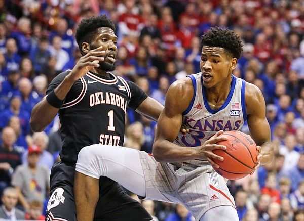 Kansas guard Ochai Agbaji (30) moves in to the bucket against Oklahoma State guard Jonathan Laurent (1) during the first half on Monday, Feb. 24, 2020 at Allen Fieldhouse.