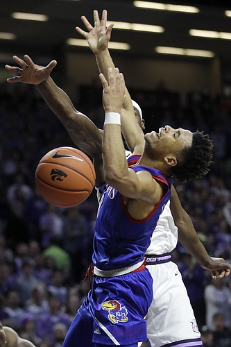 Kansas guard Devon Dotson (1) is fouled by Kansas State forward Makol Mawien, back, during the first half of an NCAA college basketball game in Manhattan, Kan., Saturday, Feb. 29, 2020. (AP Photo/Orlin Wagner)