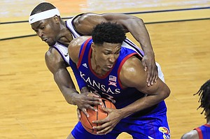 Kansas forward David McCormack (33) is fouled by Kansas State forward Makol Mawien, left, during the second half of an NCAA college basketball game in Manhattan, Kan., Saturday, Feb. 29, 2020. Kansas defeated Kansas State 62-58. (AP Photo/Orlin Wagner)