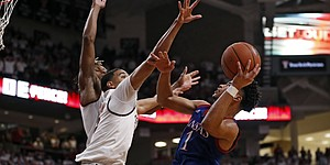 Kansas' Devon Dotson (1) shoots the ball as Texas Tech's Kevin McCullar (15) defends during the second half of an NCAA college basketball game Saturday, March 7, 2020, in Lubbock, Texas. (AP Photo/Brad Tollefson)
