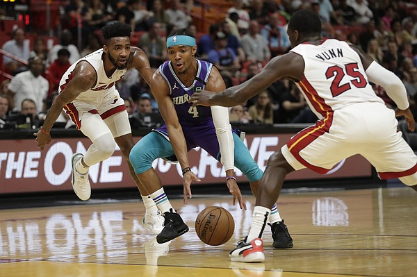 Charlotte Hornets guard Devonte' Graham (4) drives to the basket past Miami Heat guard Kendrick Nunn (25) and forward Derrick Jones Jr. during the first half of an NBA basketball game, Wednesday, March 11, 2020, in Miami. (AP Photo/Wilfredo Lee)