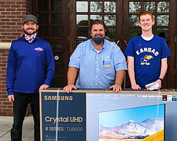 RCST Trivia champion Isaac Henderson, right, picks up his grand prize from tourney sponsor Matt Llewellyn, center, and Rock Chalk Sports Talk host Nick Schwerdt at 23rd Street Brewery.