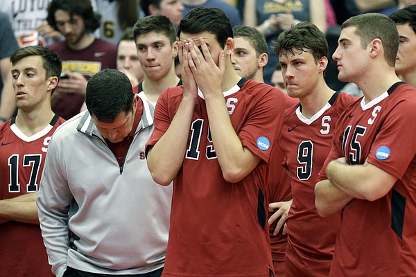 In this May 3, 2014, file photo, Stanford men's volleyball head coach John Kosty, second from left, looks down as players react after a 3-1 loss to Loyola in the NCAA men's college volleyball championship at Gentile Arena in Chicago. Stanford announced Wednesday, July 8, 2020, that it is dropping 11 sports amid financial difficulties caused by the coronavirus pandemic. The school will discontinue men's and women's fencing, field hockey, lightweight rowing, men's rowing, co-ed and women's sailing, squash, synchronized swimming, men's volleyball and wrestling after the 2020-21 academic year. Stanford also is eliminating 20 support staff positions. (AP Photo/Nam Y. Huh, File)