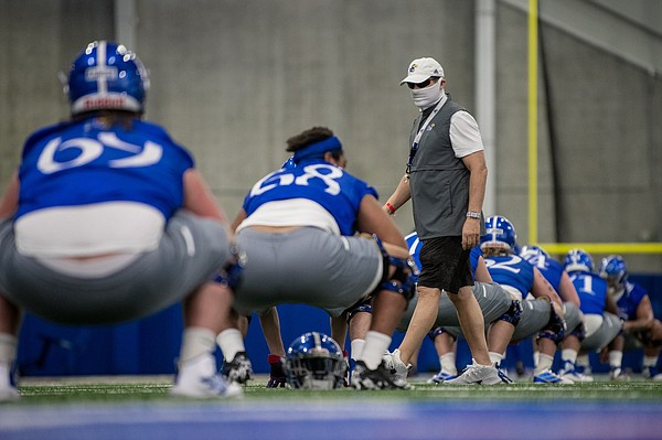 Kansas football head coach Les Miles wears a mask while walking around during an early August practice in the team's indoor facility.