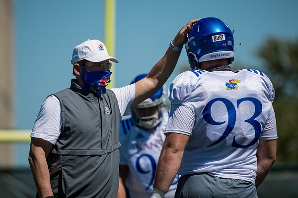 Masked Kansas football coach Les Miles pats defensive lineman Sam Burt on the head during a preseason practice in August of 2020.