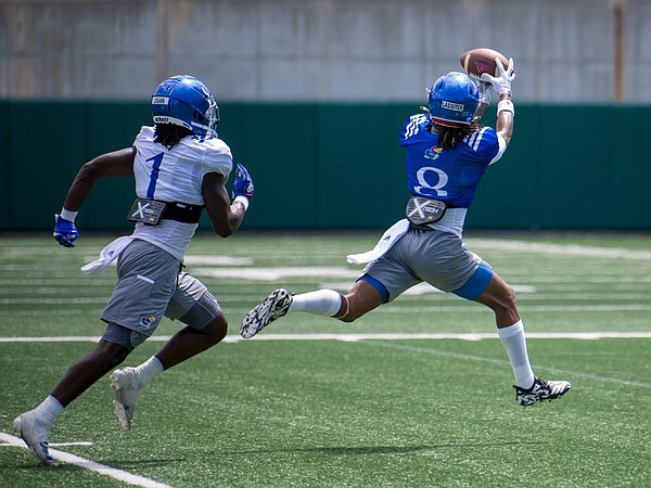 Kansas receiver Kwamie Lassiter II reaches to bring in a pass during a preseason practice in August of 2020.
