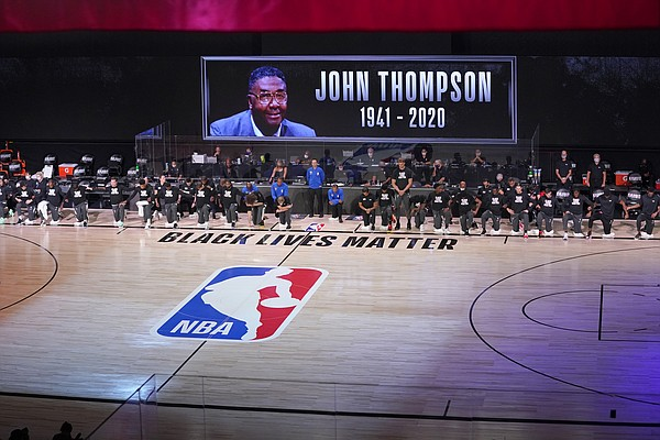 Members of the Miami Heat and the Milwaukee Bucks observe a moment of silence honoring the late John Thompson during the first half of an NBA basketball conference semifinal playoff game, Monday, Aug. 31, 2020, in Lake Buena Vista, Fla. (AP Photo/Mark J. Terrill)