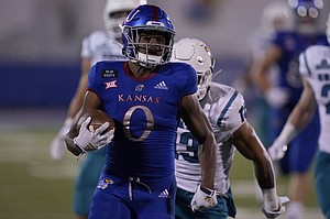 Kansas running back Velton Gardner (0) gets past Coastal Carolina safety Mateo Sudipo (13) for a 61-yard touchdown run during the second half of an NCAA college football game in Lawrence, Kan., Saturday, Sept. 12, 2020. Coastal Carolina defeated Kansas 38-23. (AP Photo/Orlin Wagner)