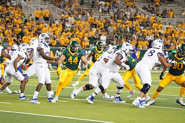 The Kansas football offensive line blocks in front of quarterback Jalon Daniels on a pass play in Waco, Texas, on Sept. 26, 2020.
