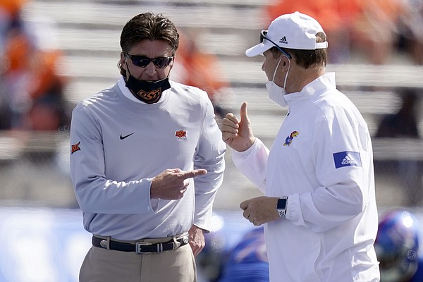 Oklahoma State head coach Mike Gundy, left, and Kansas head coach Les Miles talk before an NCAA college football game in Lawrence, Kan., Saturday, Oct. 3, 2020.