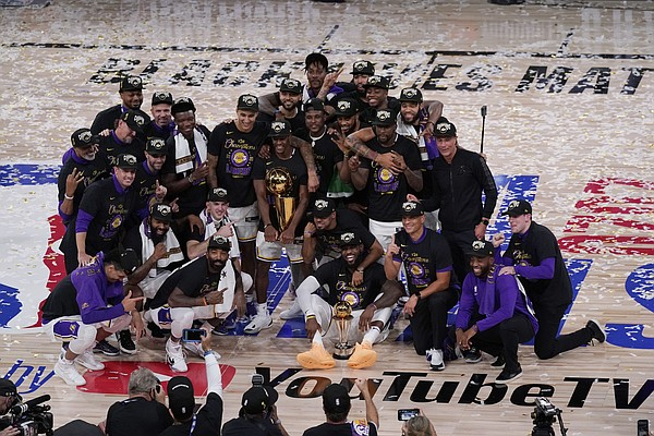 The Los Angeles Lakers players and coaches celebrate after the Lakers defeated the Miami Heat 106-93 in Game 6 of basketball's NBA Finals Sunday, Oct. 11, 2020, in Lake Buena Vista, Fla. Markieff Morris is in the bottom left of the photo with a towel around his neck and his right hand grabbing his beard. (AP Photo/John Raoux)