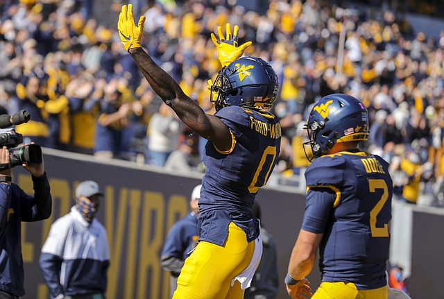 Oct 17, 2020; Morgantown, West Virginia, USA; West Virginia Mountaineers wide receiver Bryce Ford-Wheaton (0) celebrates after catching a touchdown pass during the first quarter against the Kansas Jayhawks at Mountaineer Field at Milan Puskar Stadium.