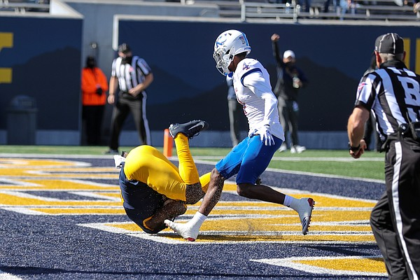 MORGANTOWN, WV - OCTOBER 17: West Virginia Mountaineers wide receiver Bryce Ford-Wheaton (0) tumbles as he makes a 33-yard touchdown catch during the first quarter of the college football game between the Kansas Jayhawks and the West Virginia Mountaineers on October 17, 2020, at Mountaineer Field at Milan Puskar Stadium in Morgantown, WV.