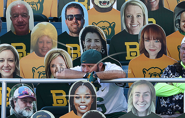 A fan watches an NCAA college football game between TCU and Baylor while seated next to cutouts in Waco, Texas, Saturday, Oct. 31, 2020. (Jerry Larson/Waco Tribune-Herald via AP)