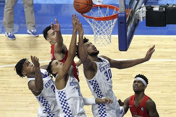 From front left to right, Kentucky's Cam'Ron Fletcher watches as B.J. Boston and Olivier Sarr try to tip the ball in as Richmond's Blake Francis looks on during the second half of an NCAA college basketball game in Lexington, Ky., Sunday, Nov. 29, 2020. (AP Photo/James Crisp)