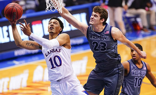 Kansas forward Jalen Wilson (10) gets under Washburn forward Will McKee (23) for a shot and a foul during the first half on Thursday, Dec. 3, 2020 at Allen Fieldhouse.