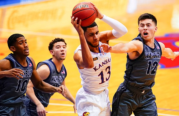 Kansas guard Tristan Enaruna (13) grabs a rebound from Washburn guard Tyler Geiman (12) during the second half on Thursday, Dec. 3, 2020 at Allen Fieldhouse.