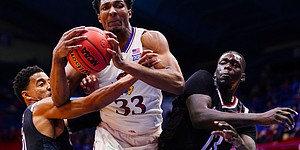 Kansas forward David McCormack (33) muscles away an offensive rebound from Omaha guard Ayo Akinwole, left, and Omaha forward Wanjang Tut (13) during the second half on Friday, Dec. 11, 2020 at Allen Fieldhouse.