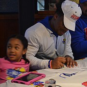 Lawrence High senior Devin Neal (middle) signs his national letter of intent while his family watches Wednesday afternoon at 23rd Street Brewery on Dec. 16, 2020. Neal, who is the top-ranked recruit in the state, signed to play football and baseball at KU.