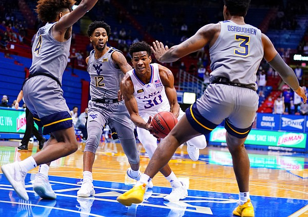 Kansas guard Ochai Agbaji (30) is surrounded in the paint by three West Virginia defenders during the first half, Tuesday, Dec. 22, 2020 at Allen Fieldhouse.
