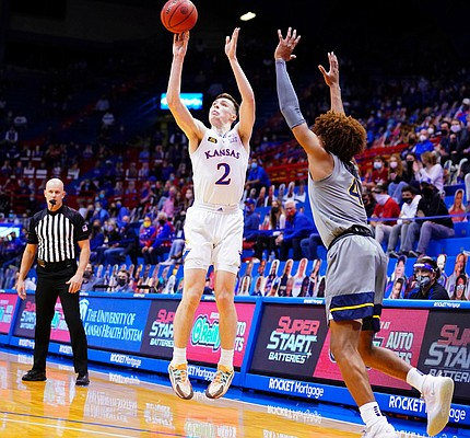 Kansas guard Christian Braun (2) puts up a three against West Virginia guard Miles McBride (4) during the first half, Tuesday, Dec. 22, 2020 at Allen Fieldhouse.