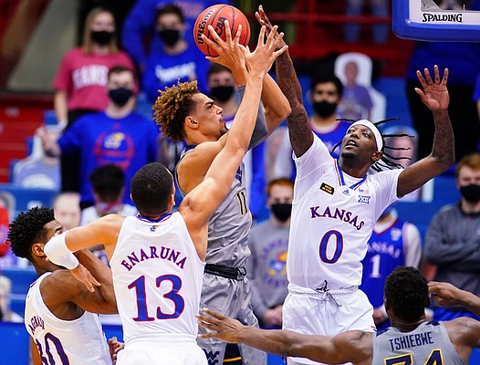 Kansas guard Marcus Garrett (0) comes in to defend against a shot from West Virginia forward Emmitt Matthews Jr. (11) during the first half, Tuesday, Dec. 22, 2020 at Allen Fieldhouse.