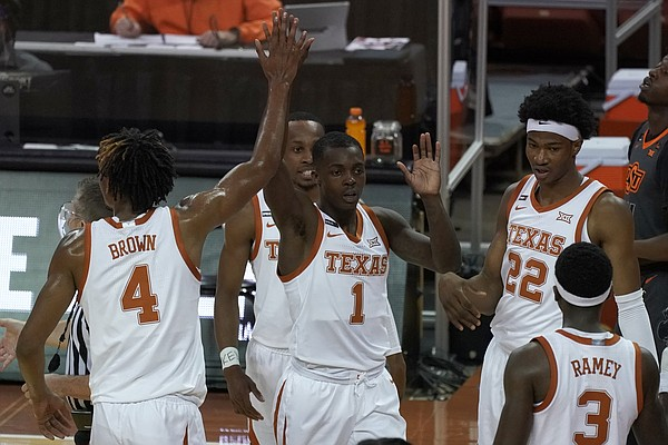 Texas' Andrew Jones (1) is congratulated by teammates, including Greg Brown (4), after making a three-point basket against Oklahoma State during the first half of an NCAA college basketball game in Austin, Texas, Sunday, Dec. 20, 2020. (AP Photo/Chuck Burton)