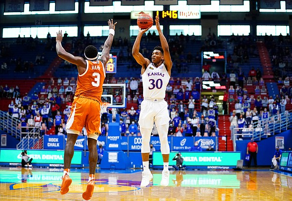 Kansas guard Ochai Agbaji (30) puts up a three over Texas guard Courtney Ramey (3) during the first half, Saturday, Jan. 2, 2021 at Allen Fieldhouse.
