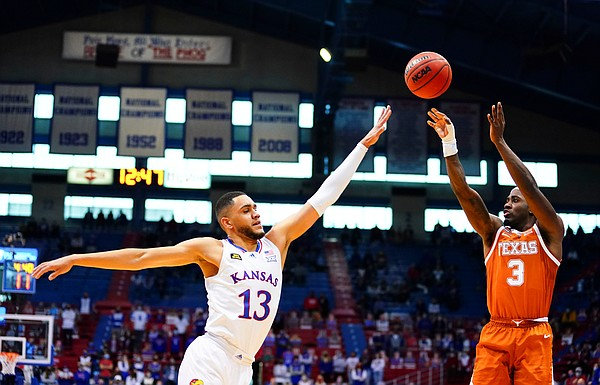 Texas guard Courtney Ramey (3) puts up a three from the wing over Kansas guard Tristan Enaruna (13) during the second half, Saturday, Jan. 2, 2021 at Allen Fieldhouse.