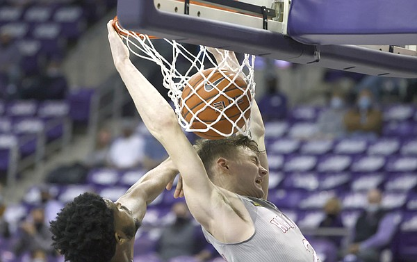 Kansas guard Christian Braun, right, dunks next to TCU center Kevin Samuel during the first half of an NCAA college basketball game Tuesday, Jan. 5, 2021, in Fort Worth, Texas. (AP Photo/Ron Jenkins)