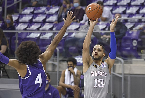 Kansas guard Tristan Enaruna (13) hits a 3-pointer over TCU guard PJ Fuller (4) during the first half of an NCAA college basketball game Tuesday, Jan. 5, 2021, in Fort Worth, Texas. (AP Photo/Ron Jenkins)