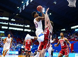Kansas guard Ochai Agbaji (30) hangs for a shot over Oklahoma guard Austin Reaves (12) as he draws a foul during the second half, Saturday, Jan. 9, 2021 at Allen Fieldhouse.