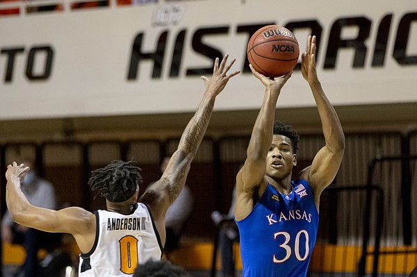 Kansas' Ochai Agbaji shoots over Oklahoma State's Avery Anderson III during the first half of the NCAA college basketball game in Stillwater, Okla., Tuesday, Jan. 12, 2021. (AP Photo/Mitch Alcala)