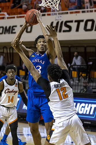 Kansas' David McCormack shoots over Oklahoma State's Matthew-Alexander Moncrieffe (12) during the first half of an NCAA college basketball game in Stillwater, Okla., Tuesday, Jan. 12, 2021. (AP Photo/Mitch Alcala)