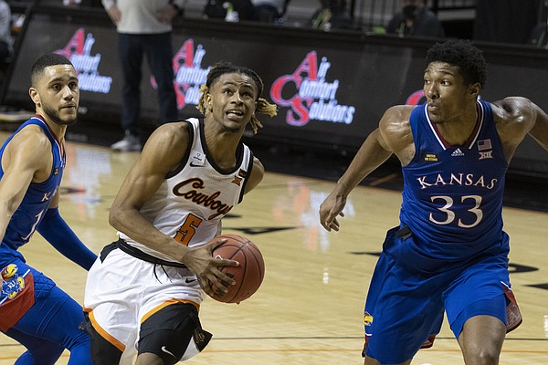 Oklahoma State's Rondel Walker (5) drives past Kansas' David McCormack (33) and Jalen Wilson (10) during the second half of the NCAA college basketball game in Stillwater, Okla., Tuesday, Jan. 12, 2021. (AP Photo/Mitch Alcala)