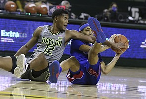 Baylor guard Jared Butler, left, battles Kansas guard Dajuan Harris for a loose ball in the first half of an NCAA college basketball game, Monday, Jan. 18, 2021, in Waco, Texas. (Rod Aydelotte/Waco Tribune-Herald via AP)