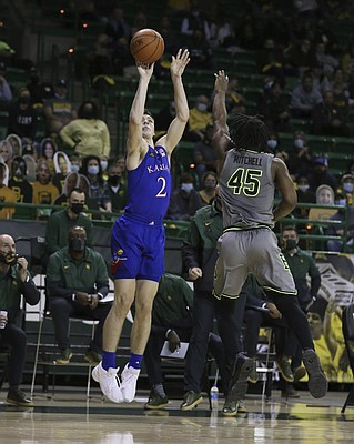 Kansas guard Christian Braun scores over Baylor guard Davion Mitchell in the first half of an NCAA college basketball game, Monday, Jan. 18, 2021, in Waco, Texas. (Rod Aydelotte/Waco Tribune-Herald via AP)