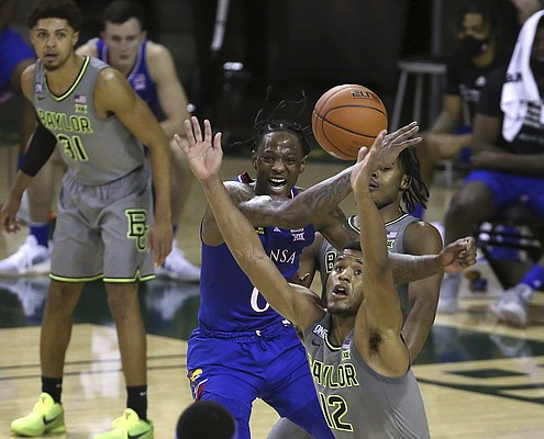 Baylor guard Jared Butler (12) and Kansas guard Marcus Garrett (0) reach for the ball in the second half of an NCAA college basketball game, Monday, Jan. 18, 2021, in Waco, Texas. (AP Photo/Jerry Larson)