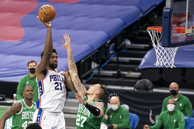Philadelphia 76ers center Joel Embiid, left, shoots over Boston Celtics center Daniel Theis during the first half of an NBA basketball game Wednesday, Jan. 20, 2021, in Philadelphia. (AP Photo/Chris Szagola)