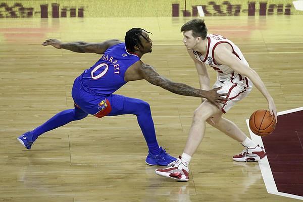 Oklahoma guard Austin Reaves (12) goes against Kansas guard Marcus Garrett (0) during the first half of an NCAA college basketball game in Norman, Okla., Saturday, Jan. 23, 2021. (AP Photo/Garett Fisbeck)