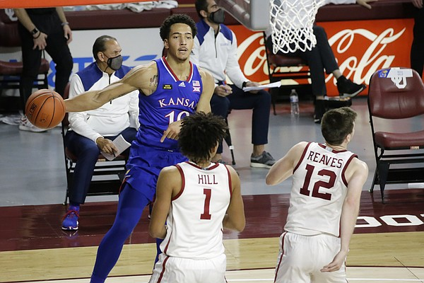 Kansas forward Jalen Wilson (10) throws the ball away from Oklahoma forward Jalen Hill (1) and guard Austin Reaves (12) during the second half of an NCAA college basketball game in Norman, Okla., Saturday, Jan. 23, 2021. (AP Photo/Garett Fisbeck)